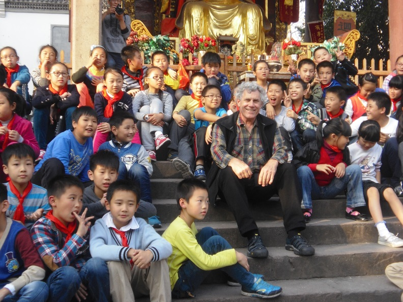 Folklorist and curator Jim Deutsch enjoys a martial arts performance along with schoolchildren at a Buddhist temple in Jinhua, Zhejiang Province.