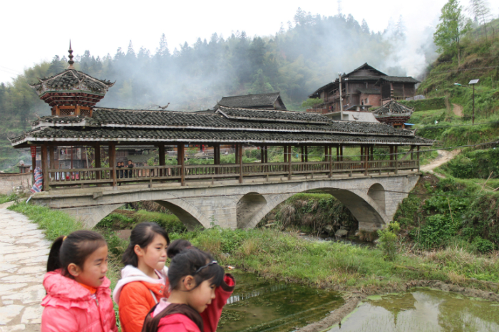 "The ""Wind and Rain"" covered wooden bridge in Dimen is a characteristic Dong village architectural feature, typically with built-in resting spots at either end. A few minutes earlier the three girls were afraid of me, then their curiosity prevailed. Photo by Atesh Sonneborn"
