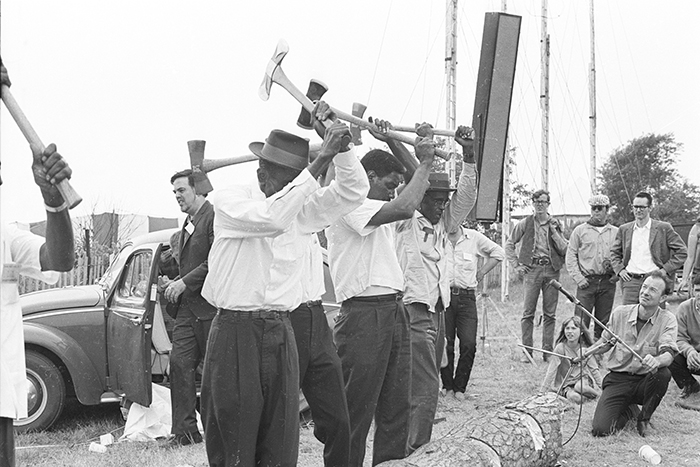 A Texas work song group performs at the 1965 Newport Folk Festival. Alan Lomax stands by the car at left, and Pete Seeger is holding a microphone at right. The singers are: Rufus Williams, Lee Protho, Charlie Coleman, Andrew Crane, and Alfred Paul East.