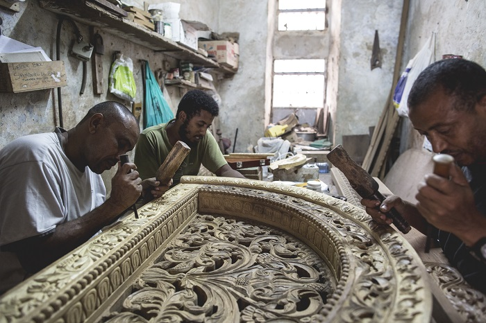 Kenyan wood carvers work on a decorative piece for over a door.