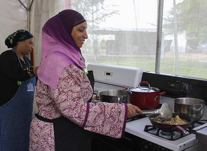 Fatma Ali Busaidy (in purple) prepares a traditional Swahili dish in the Flavors of Kenya foodways tent. Photo by Akea Brown, Ralph Rinzler Folklife Archives and Collections, Smithsonian Institution
