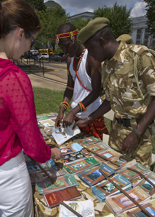A visitor, a Maasai, and a Kenyan park ranger browse pamphlets on Kenyan wildlife.