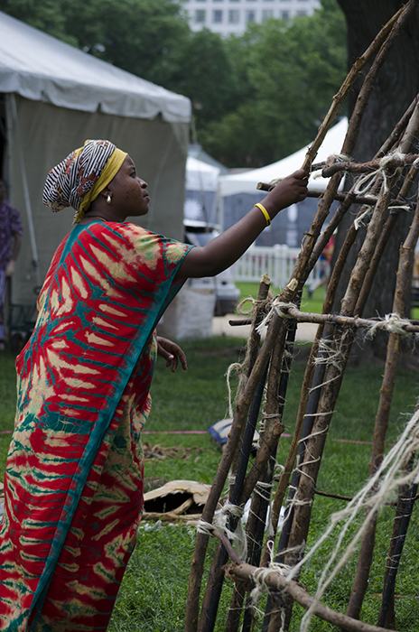 A Pokomo woman works on the frame of a domed hut, built with branches shipped from Kenya.