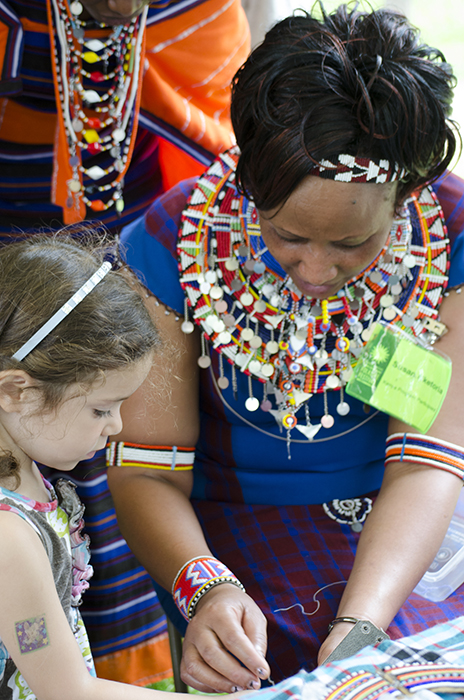 Susan Nketoria shows off bead work to a young visitor.