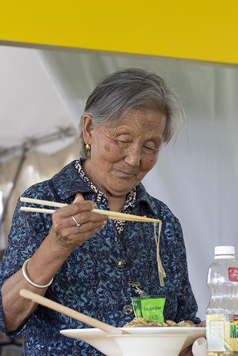 Master paper cutter Gao Fenglian enjoys some leftovers from the Five Spice Kitchen foodways demonstrations.