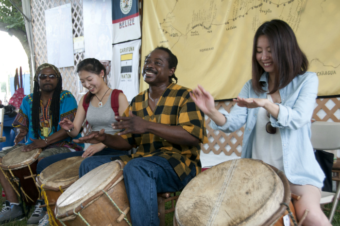Musicians Dayton and Kelsie Bernardez play drums with visitors at the 2013 Smithsonian Folklife Festival.