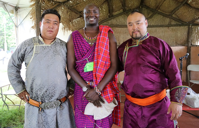 Alatenggaridi, Stephen S. Moiko, and Dabuxilatu pose for a photo after a cross-program on herding culture at the Boma Stage.