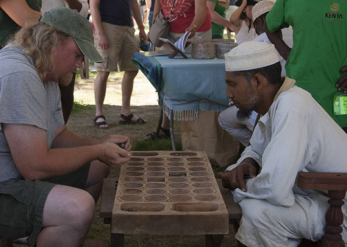 Ali Abdalla Skanda and a visitor play mancala on a hand-carved board.