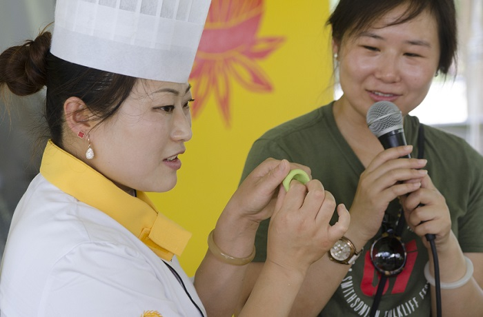 Chef Zhao Yuman molding Jade Shumai wrappers as presenter Jing Li looks on.