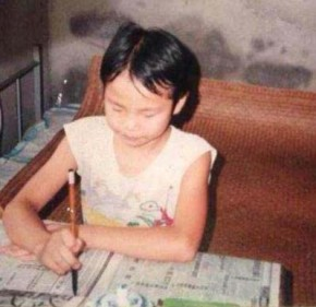 Author Qiaoyun Zhao practicing calligraphy at home in China when she was a child. Photo courtesy of Qiaoyun Zhao
