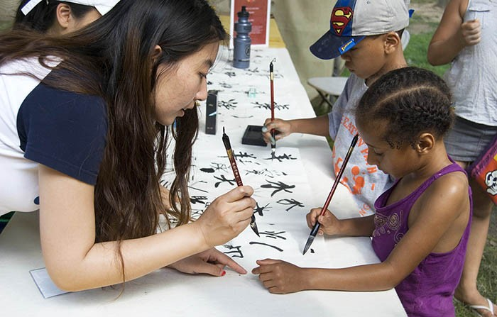 A volunteer teaches a young visitor how to write Chinese characters at the 2014 Folklife Festival. Photo by Bea Ugolini, Ralph Rinzler Folklife Archives and Collections, Smithsonian Institution