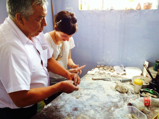 "Alfredo Lopez Morales teaching Marketplace coordinator Jackie Flanagan Pangelinan how to sculpt ""clay"" flowers in Ayacucho, Peru. Photo by Colvin English, Ralph Rinzler Folklife Archives"