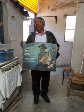 Alfredo Lopez Morales holds a retablo advertisement for Joaquin Lopez Antas, his grandfather. Photo by Jackie Flanagan Pangelinan, Ralph Rinzler Folklife Archives