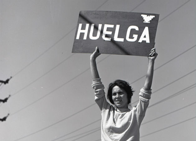 "Dolores Huerta holds up a sign indicating ""strike"" during the early days of the grape boycott, Delano, CA, 1965. This is among the materials on display in the One Life: Dolores Huerta exhibition at the National Portrait Gallery. Photo courtesy of Harvey Richards Media Archive, ©Paul Richards"