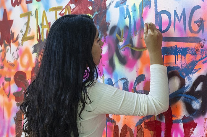 Visitors can leave their mark on the Festival near the Urban Art and Music tent, on a free-for-all mural wall. Paints are provided! Photo by Josh Weilepp, Ralph Rinzler Folklife Archives