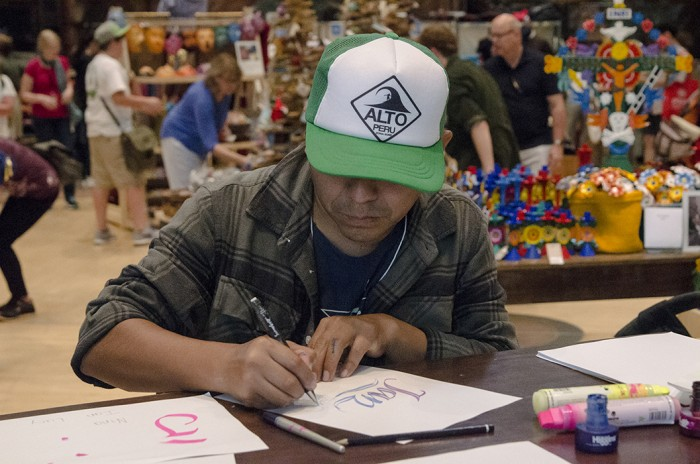 In the Marketplace, Elliot Túpac delighted visitors by writing out their names in beautiful calligraphy. Photo by Josh Weilepp, Ralph Rinzler Folklife Archives