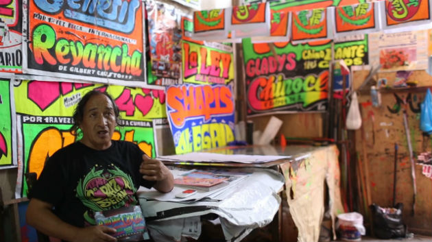 Chicha artist MONKY describes his silkscreen process in his workshop in Peru. Photo by Joshua Eli Cogan, Ralph Rinzler Folklife Archives