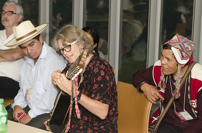 As participants, presenters, and staff took shelter inside the museum, the festivities continued in the green room. Wachiperi presenter Holly Wissler took a turn on the Cusco weavers' sixteen-string guitar. Photo by Josh Weilepp, Ralph Rinzler Folklife Archives