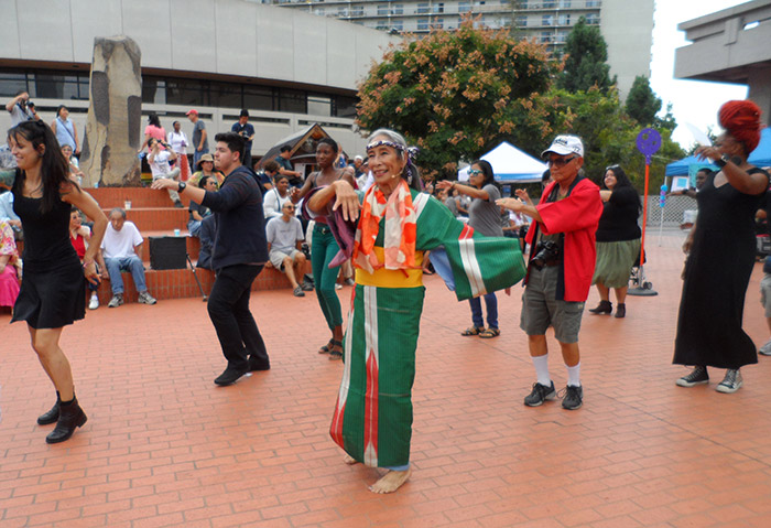 "Nobuko Miyamoto leads the dance at the <em>FandangObon</em> and Mottainai ""Eco"" Fest, held at the Japanese American Cultural and Community Center's Noguchi plaza, Little Tokyo, Los Angeles, 2015. Photo by Deborah Wong"