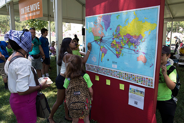 Visitors at the <em>On the Move</em> marked their birthplaces and current homes on world and U.S. maps. How long a piece of yarn is your life's journey? Photo by Francisco Guerra, Ralph Rinzler Folklife Archives