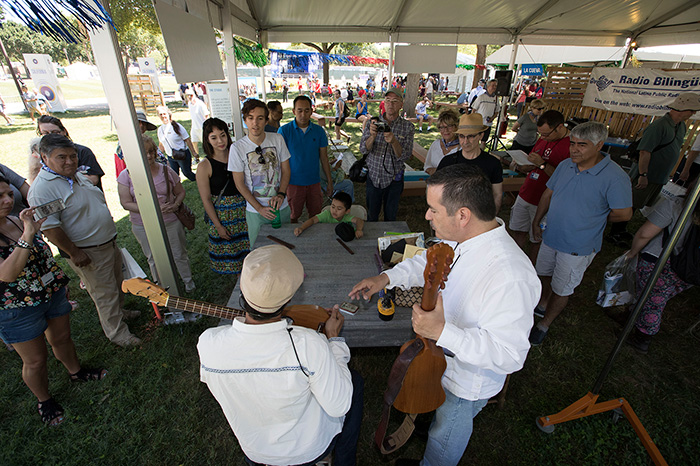 Instrument maker Ramón Gutiérrez (in white, left) had been working on building a requinto jarocho since the Festival began on Wednesday. Today he completed it, and instantly started a jam with Sounds of California presenter Russell Rodriguez (right). Photo by Francisco Guerra, Ralph Rinzler Folklife Archives