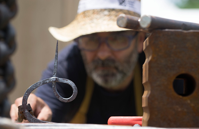 César Alcoz puts the finishing touches on a candlestick. Photo by Caroline Angelo, Ralph Rinzler Folklife Archives