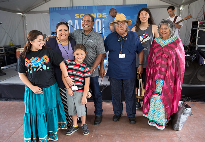 "The Rodriguezes and the Arrow-weeds pose after the ""Native Song Traditions"" performance on the Sounds of California Stage & Plaza. Photo by Francisco Guerra, Ralph Rinzler Folklife Archives"
