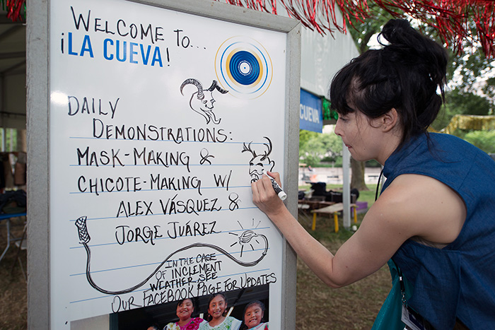 Each morning, Folklife Festival staff updates the daily schedules on whiteboard signs. Here's <em>Sounds of California</em> intern Katie Radishofski adding some <em>diablos</em> illustrations to La Cueva. Photo by Walter Larrimore, Ralph Rinzler Folklife Archives