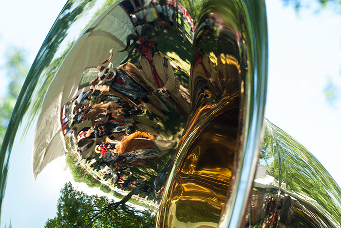 Grupo Nuu Yuku poses in the bell of Pedro Flores's sousaphone before their performance with Banda Brillo de San Miguel Cuevas at the Sounds of California Stage & Plaza. Photo by Ronald Villasante, Ralph Rinzler Folklife Archives
