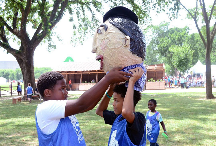 "Young visitors try on ""Charlie"" the big head after a game of sponge tag at the Txiki-Txoko. Photo by Ravon Ruffin, Ralph Rinzler Folklife Archives"