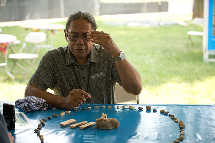 A man sits at an outdoor table, holding up one hand, presiding over a game using sticks and stones laid out in a circle in front of him.